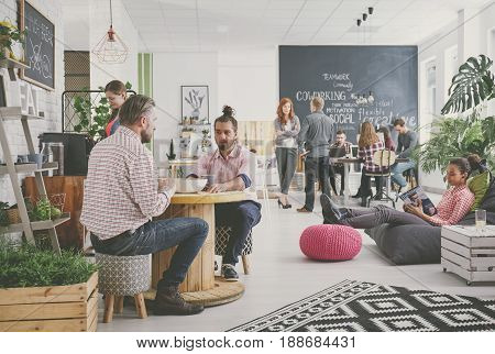 Marketing agency workers having coffee break at comfortable relax zone poster