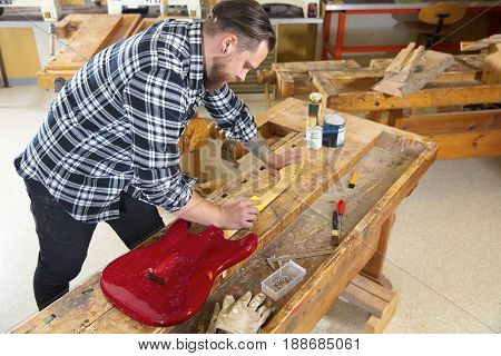 Carpenter using sanding paper on a guitar neck in a workshop for wood. Hard working man with tattoo and beard working with musical instrument restoration.