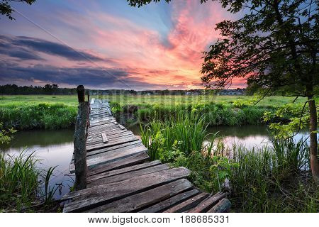 Old wooden bridge across the river under the dramatic dawn sky