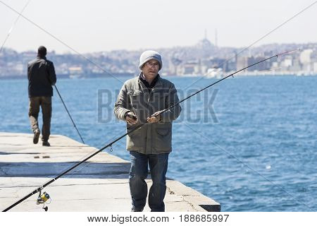 ISTANBUL, TURKEY - 3 APRIL , 2017: Fishermen are fishing on the banks of the Bosphorus in Istanbul Turkey