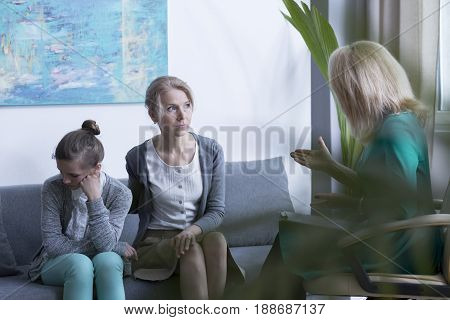 Psychotherapist talking with worried mother and shy daughter