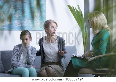 Worried mother visiting psychotherapist with her teenage daughter