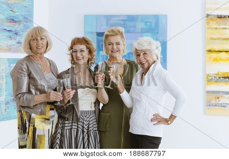 Group of happy elegant women spending time in museum