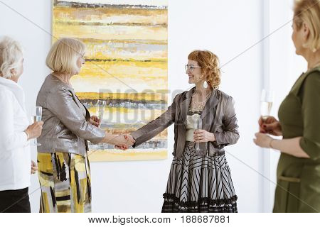 Senior woman shaking hands with curator of exhibition in gallery