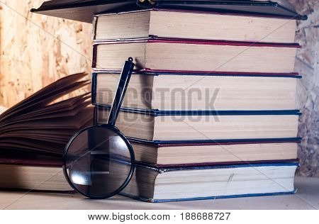 Magnifying glass and books, stacks of battered books on a wooden table. magnifier with black frame