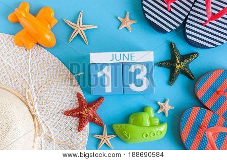 June 13th. Image of june 13 calendar on blue background with summer beach, traveler outfit and accessories. Summer day.