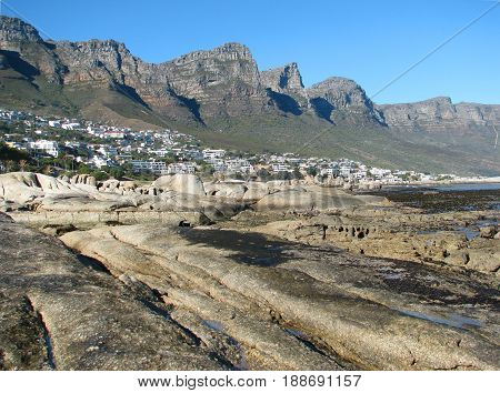 FROM CAPE TOWN, SOUTH AFRICA, HUGE BOULDERS IN THE FORE GROUND, WITH A MOUNTAIN  IN THE BACK GROUND, WHICH IS PART OF THE TABLE MOUNTAIN NATIONAL PARK