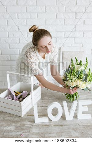 Florist show flower bouquet in shop. Young girl proposes to buy a bridal bunch of white flowers in a workshop. Light decorator studio with brick wall on background.
