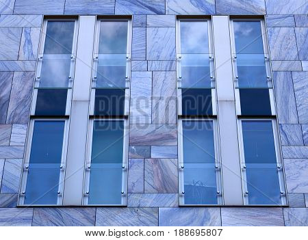Facade Of Modern Building With Blue Marble Tiles And Panes