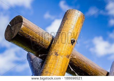 Sturdy wooden swing cross member against the sky