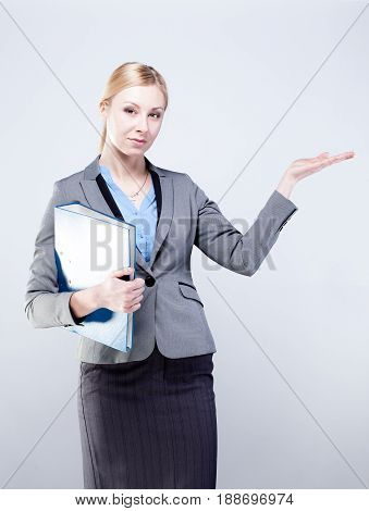 Young business woman pointing open hand palm towards blank space isolated on grey background.