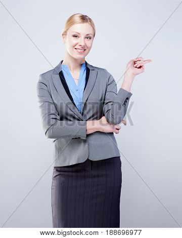 Smiling business woman pointing her finger towards blank space isolated on grey background.