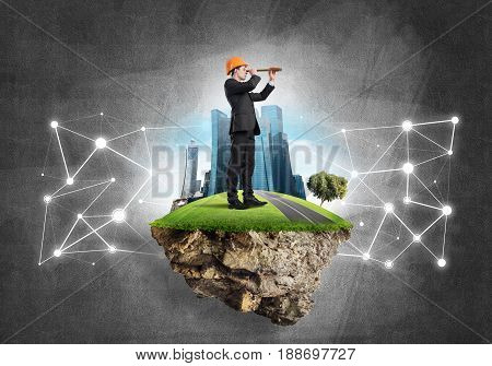 Engineer man on flying green island against concrete background