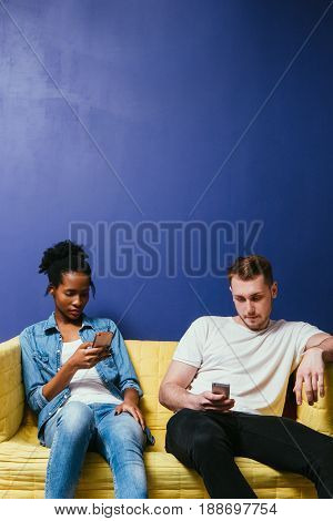 Social network addiction concept. Young interracial couple in conflict. Total ignore, not talk, sit with mobile phone. Detached white man and black woman on couch on blue background.