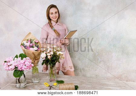 Smiling florist with check list in froristry shop. Business woman with notebook in flower shop. Small business management, female manager, time management, flower sales concept