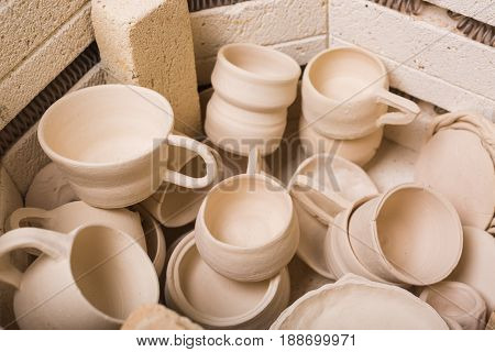 pottery, workshop, ceramics art concept - top view on unbaked clay utensils in electric oven, the jugs and cups in the kiln, some unfinished pots and bowls