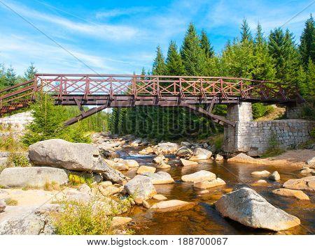 Wooden pedestrian bridge over river Jizera full of granite boulders. Czech-Polish border between Jizerka and Orle village in Jizera mountains, Czech Republic, Poland.
