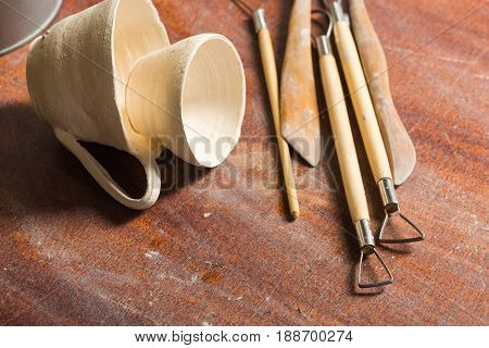 pottery, workshop, ceramics art concept - closeup on two unfired clay small cups and sculpting tools set on wooden table, clay stacks, some profiles, top view