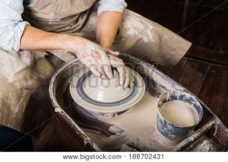 pottery, workshop, ceramics art concept - closeup on working potter's wheel with raw clay and man hands, a male sculpt a utensil with fingers, master in apron, top view