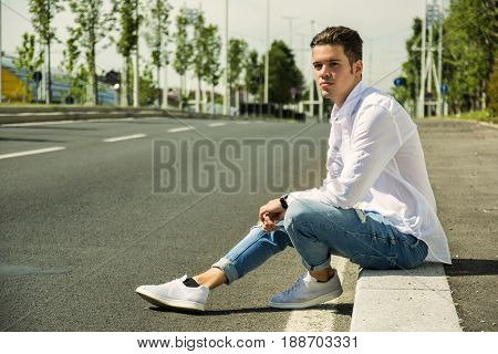 Attractive smiling man sitting on curb of city street's sidewalk, looking to a side