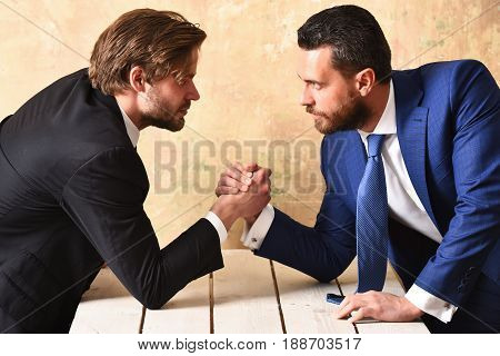 Business rivalry. Businessmens in suits arm wrestling at office.