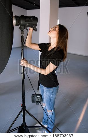Girl photographer adjust light in studio. Beautiful woman with camera is setting photographing equipment getting ready for a photo shoot