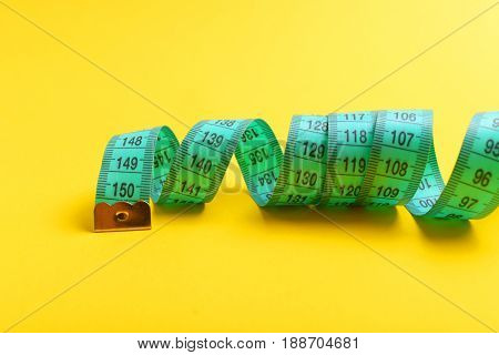 Measuring Tape In Striking Cyan Colour Twisted On Yellow