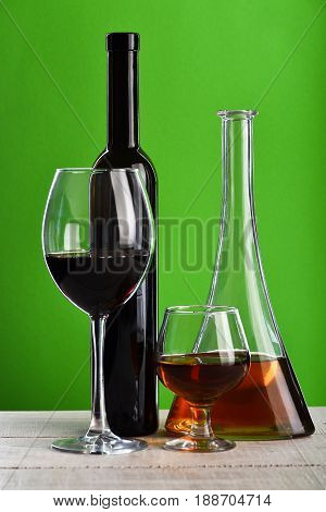 Bottles And Glasses With Wine And Whiskey On Wooden Surface