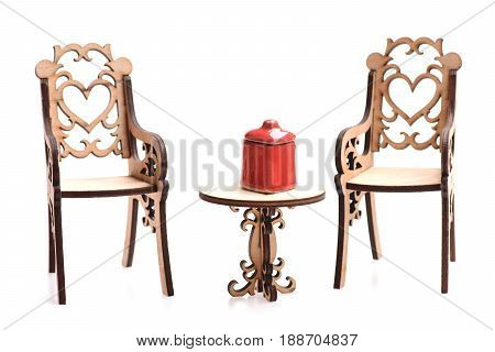 Chairs and table for decoration made of wood and small red ceramic sugar bowl for tiny kitchen isolated on white background close up. Vintage and romance concept