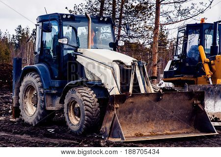skid loader working on road construction. Concept of clearing the territory of fields and forests