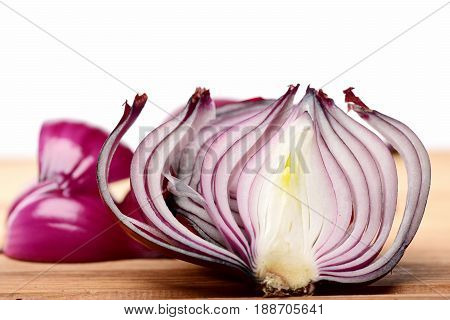 Half Of Red Onion With Separate Slices And Pieces Behind