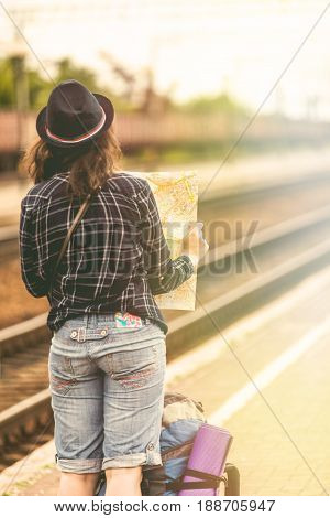 Traveler is waiting at the railway station. Travel concept. Woman sitting with map compass and travel bag at the train station. Traveler holding map and planing for next trip. Traveler reading map