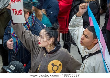 Two young people protests rising signs. Stockholm, Sweden - January 21 2017: Close up image of two young multi ethnic activists at a public square holding sign and flag about to join a demonstration.