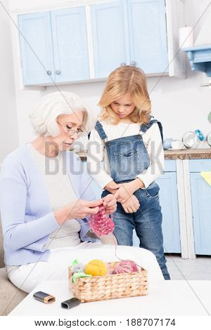 Grandmother knitting socks with her granddaughter at home. Modern granny teaching her grandchild how to knit clothes.