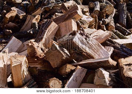 Closeup shows a wood pile of cut split oak logs.