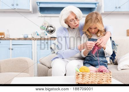 Grandmother teaching her granddaughter to knit woollen socks while staying in living room at home. Grandmother spending her free time with granddaughter.
