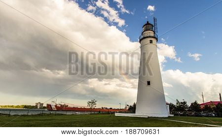 Port Huron, Michigan, USA - May 29, 2017: The Fort Gratiot Lighthouse with a rainbow and a Great Lakes Freighter on the coast of Lake Huron.