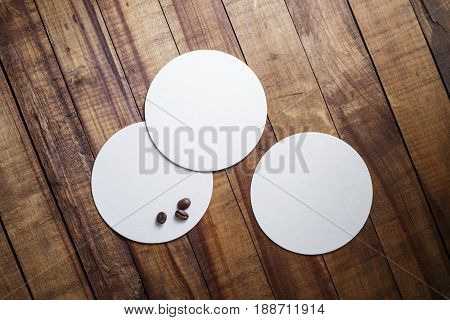 Blank square beer coasters and coffee beans on vintage wood table background. Top view.