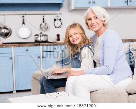 Little granddaughter typing on laptop computer and sitting with her granny on sofa. Granny and little girl expressing surprise or success after log in somewhere.