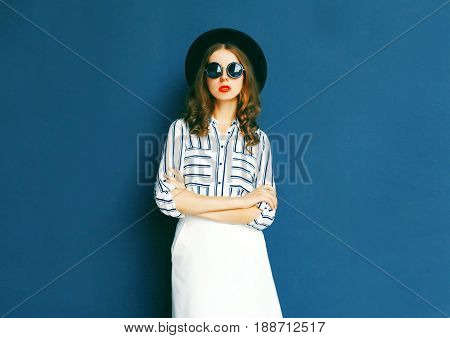 Fashion Pretty Woman Wearing A Black Sunglasses, Hat And White Skirt Posing Over A Gray Background