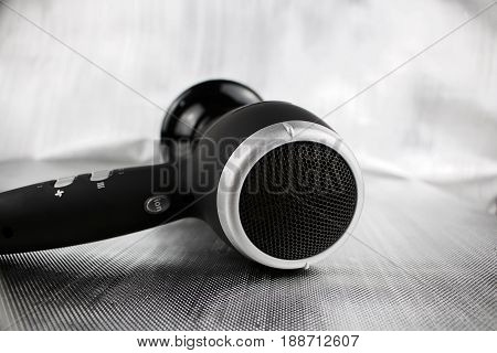 Big black and silver hair dryer on the silver background. poster