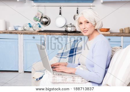 Grandmother writing letter to her family using email. Pretty grandmother using laptop computer at home.