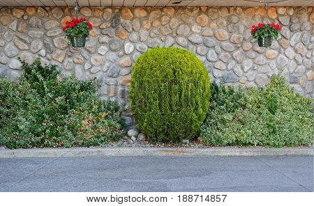 Riverstone wall with decorative bushes and hanging flower pot