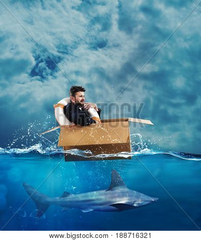 Fearful Businessman on a cardboard in the sea with under a shark