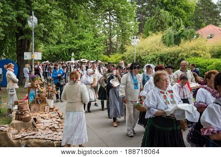 PIESTANY SLOVAKIA - MAY 20 2017: A crowed of artisans dressed in folk costumes marches down the street in the park during the artisan festival in Piestany