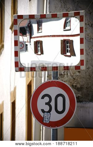 On the buildings of a blind crossing hangs a traffic mirror and a speed limit sign.