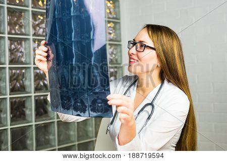 Woman Doctor Looking at X-Ray Radiography in doctor's office.