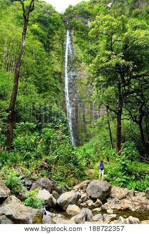 Young Female Tourist Hiking To The Famous Waimoku Falls At The Head Of The Pipiwai Trail, Above Seve