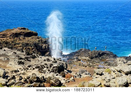 Tourists Admiring The Nakalele Blowhole On The Maui Coastline. A Jet Of Water And Air Is Violently F