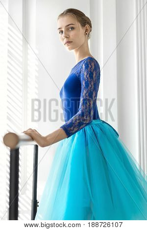Cute ballerina stands next to the ballet barre and holds her hand on it on the white wall background. She wears a lace blue leotard with a cyan tutu and looks into the camera. Indoors.